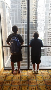 The boys looking out from the 5th floor hotel window above Dallas Street, Houston, TX